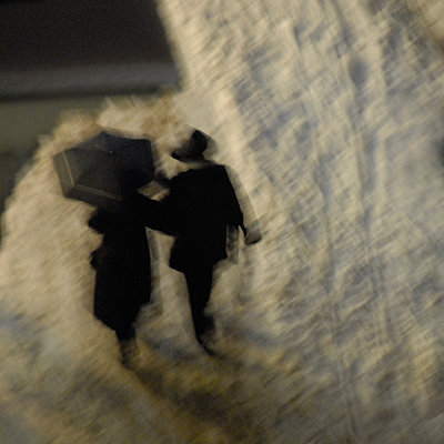 Couple with umbrella at twilight, blurred motion - p1624m2195931 by Gabriela Torres Ruiz