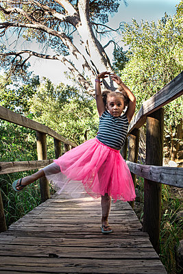 Little girl in pink tulle skirt shows a dance pose - p1640m2246839 by Holly & John