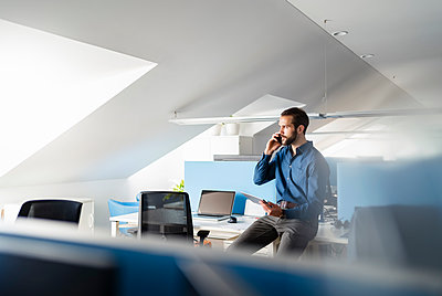 Entrepreneur with digital tablet talking on mobile phone at office - p300m2264894 by Daniel Ingold
