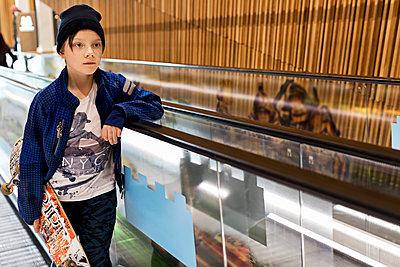 Boy with skateboard on escalator - p312m1495423 by Susanne Kronholm