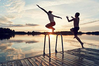 Boys jumping into lake - p312m1521852 by Johan Alp