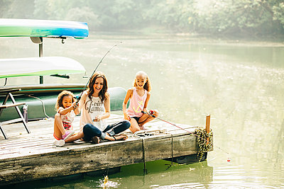 Mother and daughters fishing in lake - p555m1306250 by Inti St Clair