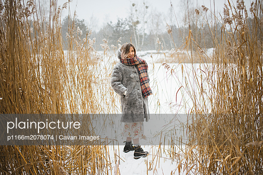 girl in the winter on a lake in the middle of reeds - p1166m2078074 by Cavan Images