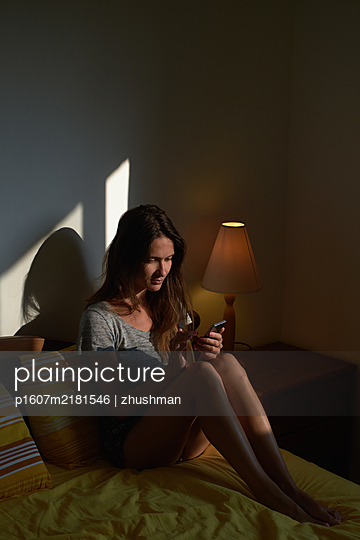 Woman with smartphone sit on bed in the bedroom - p1607m2181546 by zhushman