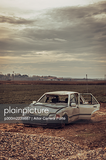 Clouds over white wrecked car abandoned in middle of field - p300m2239887 by Aitor Carrera Porté