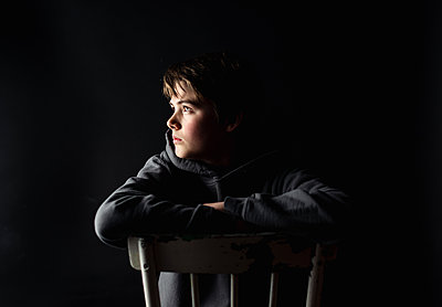 Low key portrait of adolescent boy sitting on a chair in a dark room. - p1166m2191929 by Cavan Images