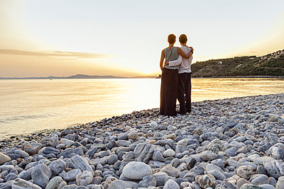 Greece, Pelion, couple enjoying at sunset at beach - p300m1587205 by Maria Maar