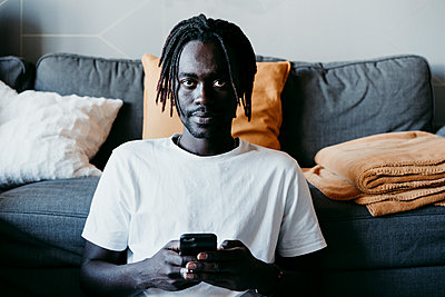 Young man holding mobile phone while sitting against sofa in living room - p300m2240244 by Eva Blanco