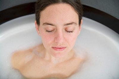 Woman with brown hair lying in bathtub - p3013815f by Stella