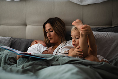 Mother with kids in bed - p312m2052630 by Anna Johnsson