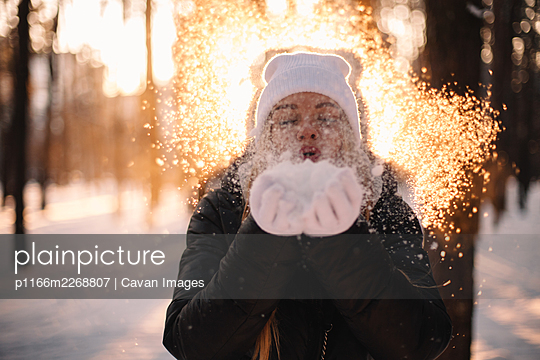 Woman blowing snow standing in park at sunset during winter - p1166m2268807 by Cavan Images