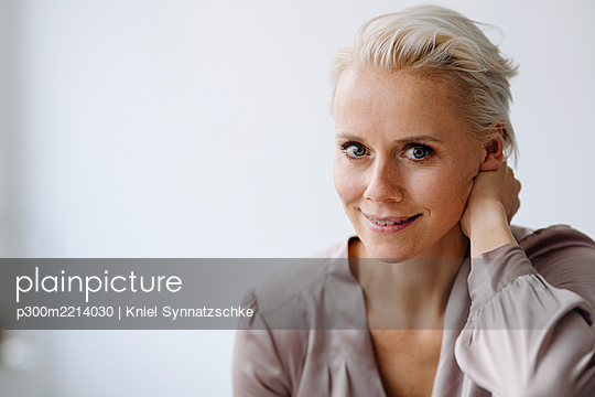 Close-up of confident businesswoman against white wall in office - p300m2214030 by Kniel Synnatzschke
