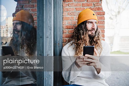 portrait of handsome man sitting by window, Madrid, Spain - p300m2274031 von Eva Blanco