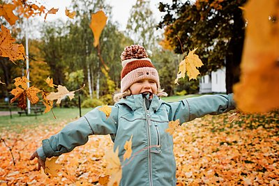 young girl laughing and throwing fall leaves into the air - p1166m2141081 by Cavan Images