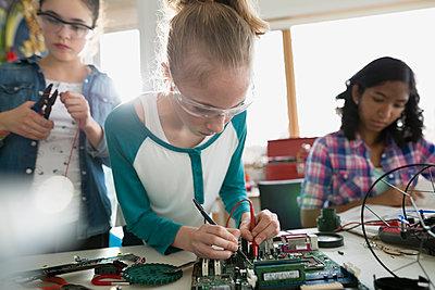 Focused girls assembling circuit board - p1192m1129543f by Hero Images