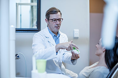Dentist with dental mold talking to patient - p300m1189249 by zerocreatives