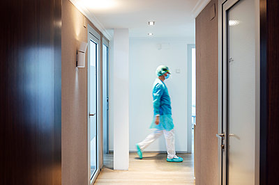 Mature male dentist walking in illuminated hallway at medical clinic - p300m2198387 by Jose Luis CARRASCOSA