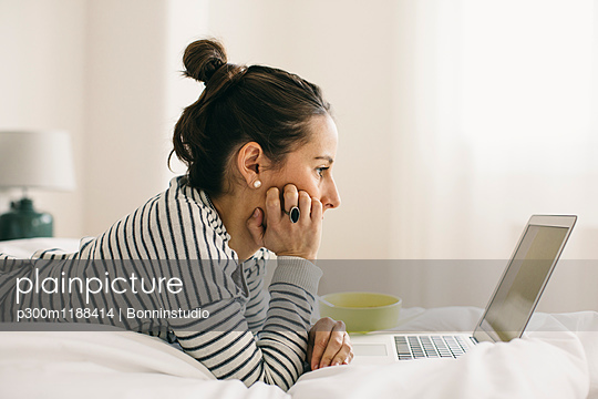 Relaxed woman lying in bed using laptop