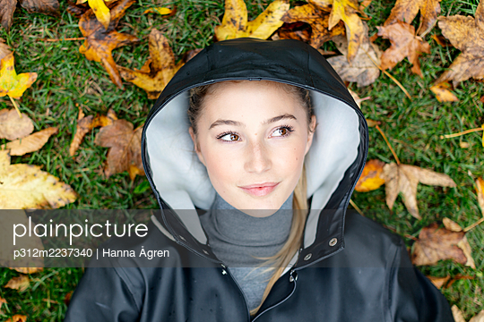 Young woman lying on autumn leaves - p312m2237340 by Hanna Ågren