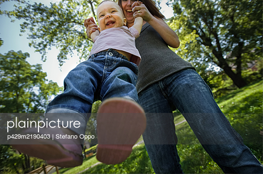 Low angle view of mother and baby girl playing on a lawn in a park. - p429m2190403 by Stefano Oppo