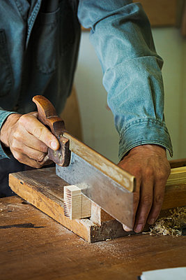 A craftsman using a handsaw on a piece of wood.  - p1100m1522491 by Mint Images
