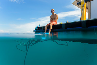 Man sitting on platform wearing flippers - p300m1470092 by Konstantin Trubavin