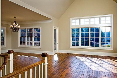 Empty great room with hardwood floors - p5551491f by Blend Images