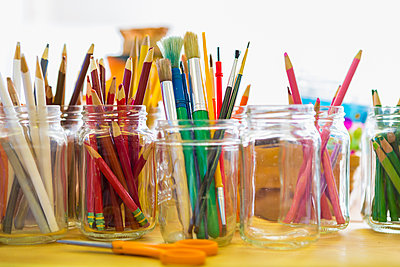 Close up of jars of colored pencils and paintbrushes - p555m1413771 by Marc Romanelli