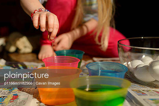 Girl mixing colors in bowl while sitting on floor at home - p1166m1182966 by Cavan Images