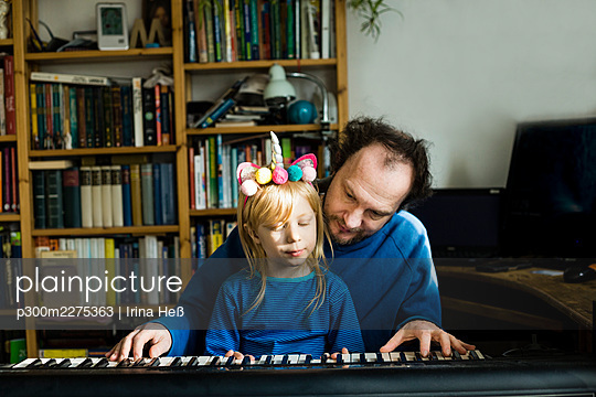 Man teaching synthesizer to daughter while sitting at home - p300m2275363 by Irina Heß
