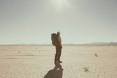 Male backpacker hiking in vast desert, Black Rock Desert, Nevada - p1100m1216346 by Mint Images
