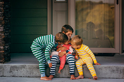 Loving brothers kissing sister in front of house - p1166m1403060 by Cavan Images