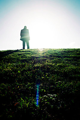 Silhouette of man standing in grassy field - p597m2026530 by Tim Robinson