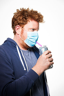 Man with surgical mask and beverage can, portrait - p930m2253770 by Ignatio Bravo