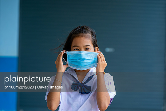 Asian children in school uniform wearing protective mask to Prot - p1166m2212820 by Cavan Images