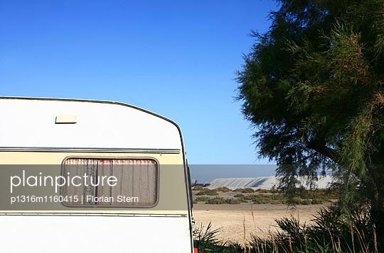 Vorhang in einem Wohnwagen, im Hintergrund die Saline von Giraud, Camargue, Frankreich, Europa - p1316m1160415 von Florian Stern