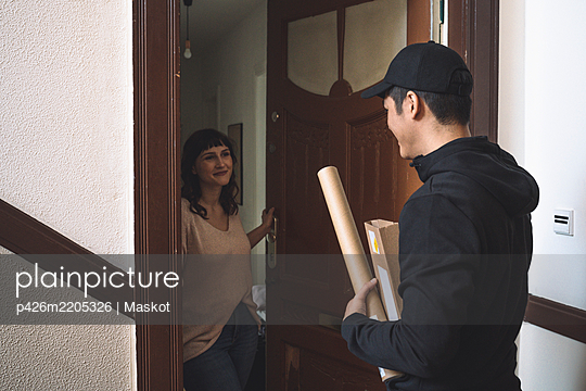 Smiling customer talking to delivery man at doorstep - p426m2205326 by Maskot