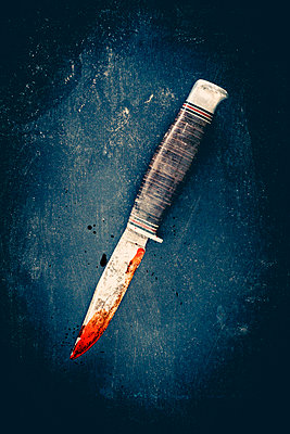 An old knife with blood on the blade, lying on a dirty black surface. - p1302m2089436 by Richard Nixon