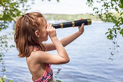Mädchen blickt durch Fernrohr am See - p1394m1541473 von benjamin tafel