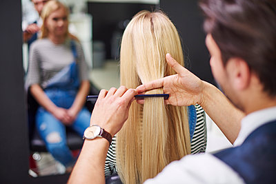 Rear view of hairdresser combing woman's hair - p300m1587051 by gpointstudio