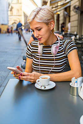 Italy, Florence, portrait of young woman at pavement cafe looking at smartphone - p300m2042755 von Giorgio Magini
