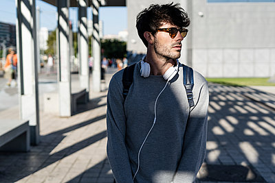 Man with sunglasses and headphones looking around in the city - p300m2140460 by Giorgio Fochesato