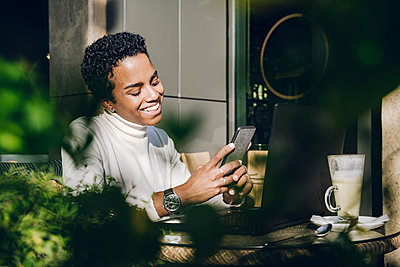 Happy businesswoman using mobile mobile phone at cafe on sunny day - p300m2241420 by Katharina und Ekaterina