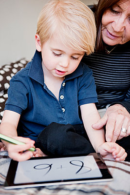 Grandmother and grandson using digital tablet - p312m1075902f by Peter Rutherhagen