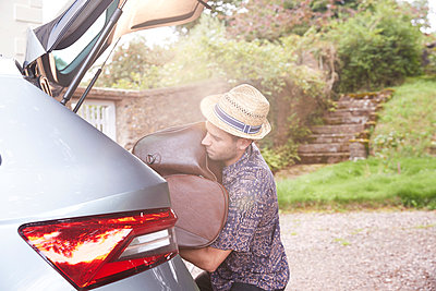 Young man in trilby removing luggage from car boot outside hotel - p429m2023315 by Peter Muller