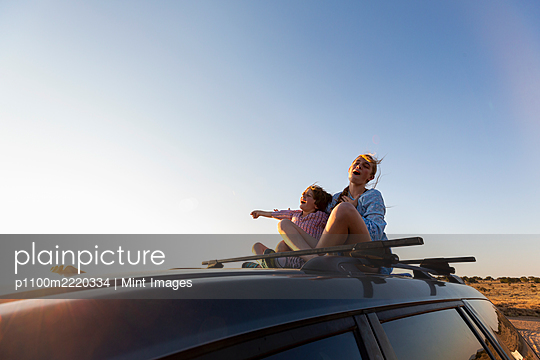 Teenage girl and her younger brother  on top of SUV on desert road, Galisteo Basin, Santa Fe - p1100m2220334 by Mint Images
