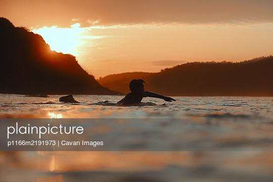 Surfer in sea at sunset, Lombok, Indonesia - p1166m2191973 by Cavan Images