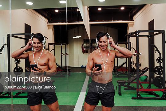 Mid adult athlete using mobile phone while adjusting headphones in gym - p300m2274530 by Eva Blanco