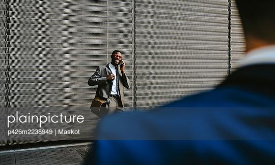 Male entrepreneur talking on smart phone against metal grate - p426m2238949 by Maskot