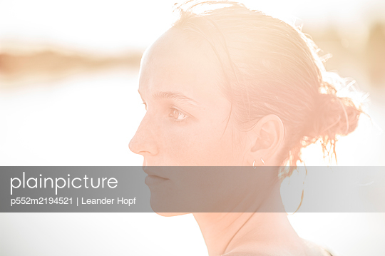 Portrait of young woman against the light - p552m2194521 by Leander Hopf